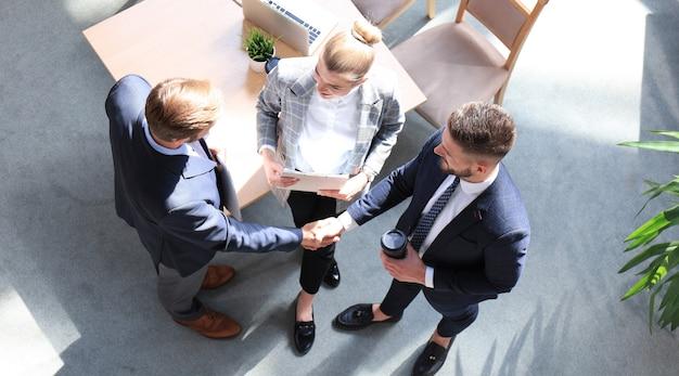 Widok z góry dwóch mężczyzn ściskających dłonie, podczas gdy młoda kobieta patrzy na nich i uśmiecha się.
