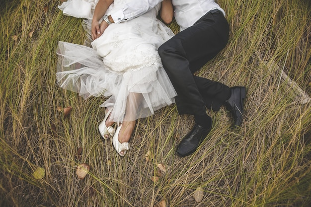 Widok z góry dwóch nowożeńców leżąc na trawie obejmując sobą.