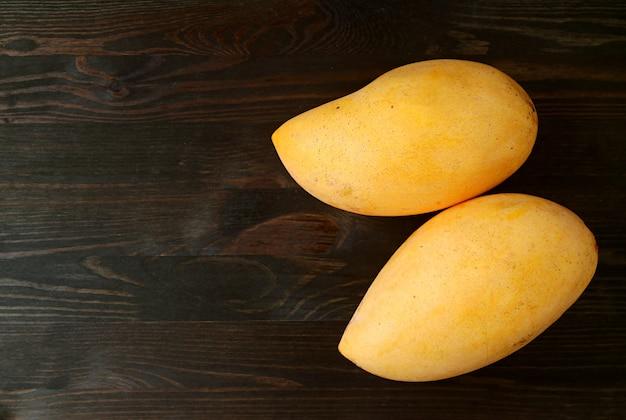 Widok z góry dwóch świeżych dojrzałych owoców mango na białym tle na czarnym tle drewnianych