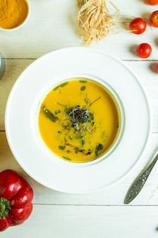 Widok z góry dyniowej zupy w białym pucharze