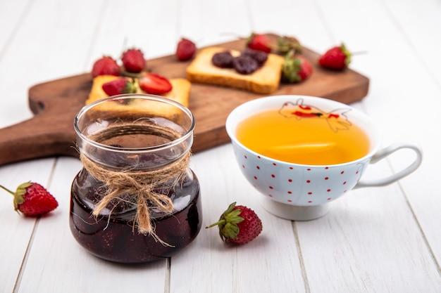 Widok z góry dżemu truskawkowego przy filiżance herbaty ze świeżymi truskawkami na białym tle drewnianych