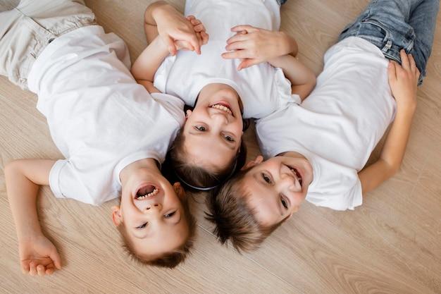 Widok z góry dzieci uśmiechnięte i leżące na podłodze