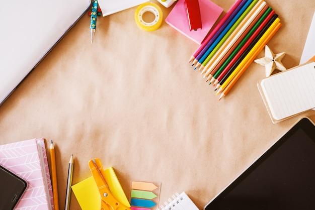 Widok z góry dziecięcego szkolnego biurka z drewnianymi kredkami do sztuki i nowoczesnymi technologiami do przeglądania.