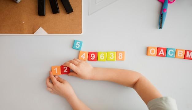 Widok z góry dziecka na biurko uczenia się cyfr i liter