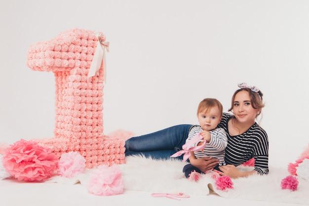 Widok z góry, dziecko w ramionach matki siedzącej w sukienkach na podłodze wśród cyfr 1.