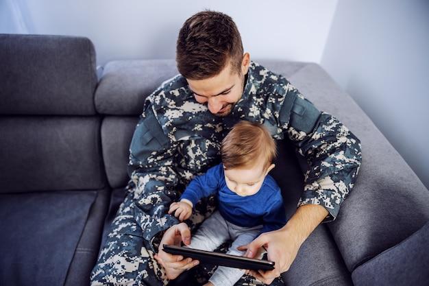 Widok z góry dzielnego żołnierza nadrabiającego stracony czas z synem. mężczyzna trzyma malucha na kolanach, tablet w rękach i ogląda bajki.