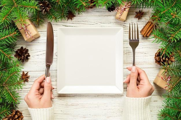 Widok z góry dziewczyna trzyma w ręku widelec i nóż i jest gotowa do jedzenia. pusty biały kwadratowy talerz na drewnianym bożego narodzenia tle. świąteczny obiad danie z wystrojem nowego roku