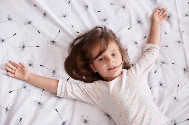 Widok z góry dziewczynki leżącej w łóżku i rozkładającej ręce na białej okładce z mniszkiem lekarskim, urocze dziecko z ciemnymi włosami w piżamie