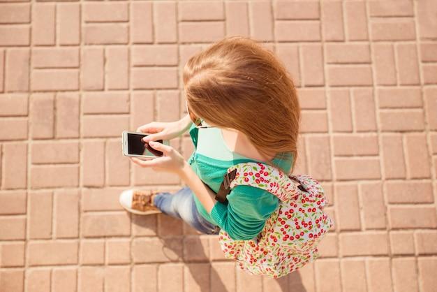 Widok z góry dziewczyny chodzenie po kostce brukowej i pisania sms