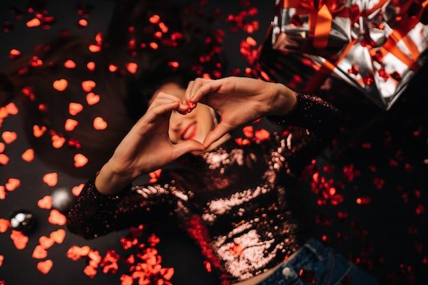 Widok z góry dziewczyny leżącej w błyszczących ubraniach na podłodze w konfetti w formie serc i pokazującej jej serce rękami.