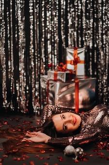 Widok z góry dziewczyny leżącej w błyszczących ubraniach na podłodze w konfetti w postaci serc i prezentów.