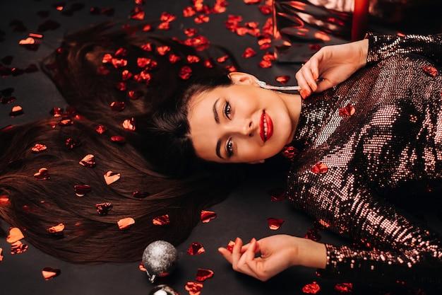 Widok z góry dziewczyny leżącej w lśniących ubraniach na podłodze w konfetti w formie serc