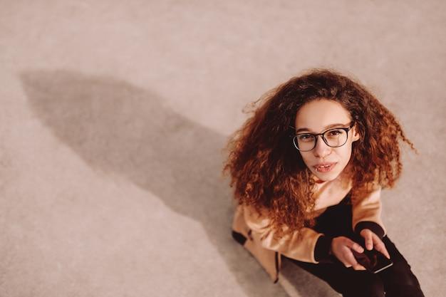 Widok z góry dziewczyny piękne mieszane rasy hipster z uśmiechem toothy za pomocą smartfona