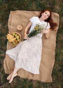 Widok z góry dziewczyny w białej sukni z bukietem stokrotek i koszem owoców