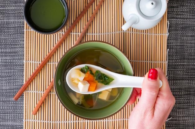Widok z góry dziewczyny z czerwonymi paznokciami, jedzącej zupę miso