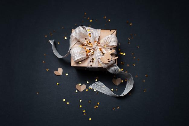 Widok z góry ekologicznego pudełka ozdobionego złotymi gwiazdkami i papierami w kształcie serc, na powierzchni w kolorze czarnym