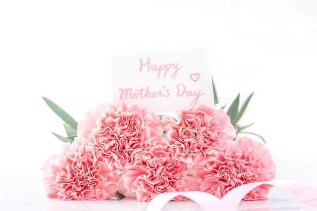 Widok z góry elegancji kwitnących słodkich różowych goździków delikatnych na białym tle na jasnym białym tle z kartą, może dzień matki pozdrowienie koncepcja projektu, zbliżenie, kopia przestrzeń