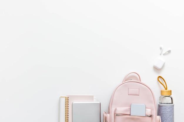 Widok z góry elegancki różowy plecak studencki pełen materiałów na białym tle. koncepcja powrotu do szkoły