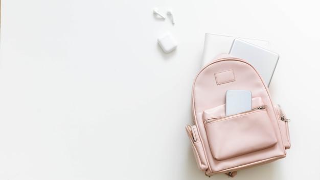 Widok z góry elegancki różowy plecak studencki pełen materiałów na białym tle. powrót do koncepcji szkoły