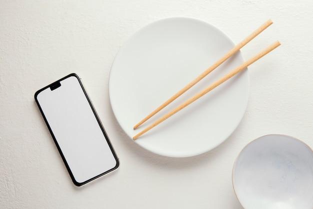 Widok z góry eleganckiej zastawy stołowej ze smartfonem