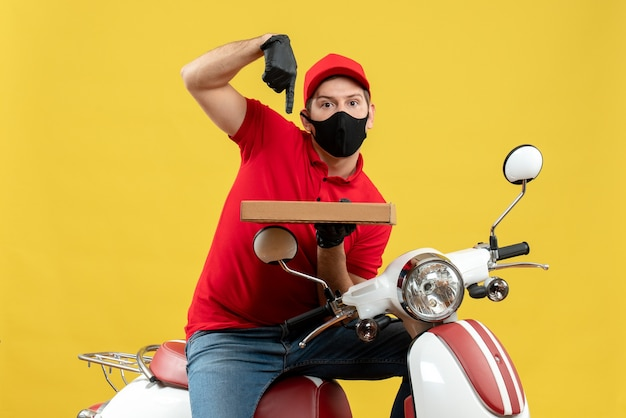 Widok z góry emocjonalny ambitny kurier człowiek ubrany w czerwoną bluzkę i rękawiczki kapelusz w masce medycznej siedzi na skuter wskazując kolejność