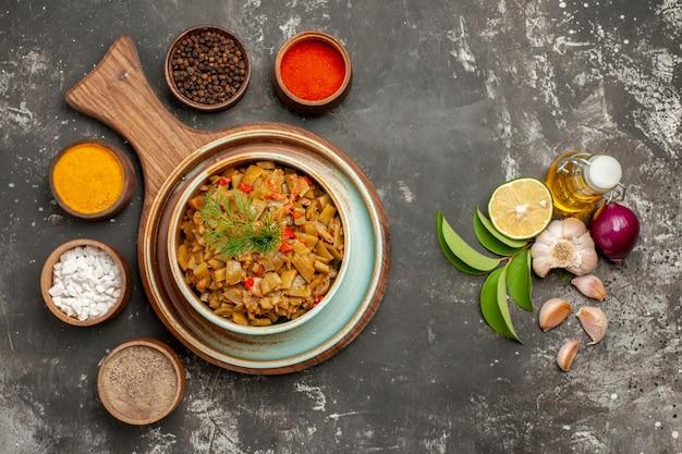 Widok z góry fasolka szparagowa z pomidorami pomidory i fasolka szparagowa na talerzu i trzy rodzaje przypraw obok butelki oleju czosnek cebula cytryna i liście