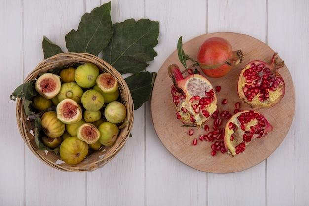 Widok z góry figi w koszu z liśćmi i granatów na desce do krojenia na białym tle