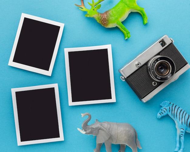 Widok z góry figurek zwierząt z aparatem i zdjęciami na dzień zwierząt