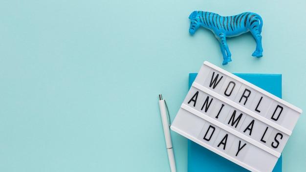 Widok z góry figurki zebry z podświetlanym pudełkiem i piórem na dzień zwierząt