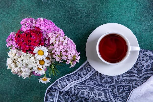 Widok z góry filiżanka herbaty na ręcznik kuchenny z kolorowymi kwiatami na zielono