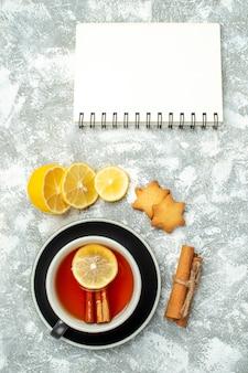 Widok Z Góry Filiżanka Herbaty Plasterki Cytryny Laski Cynamonu Notes Na Szarej Powierzchni Darmowe Zdjęcia