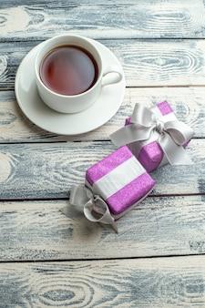 Widok z góry filiżanka herbaty świąteczne prezenty na drewnianym tle