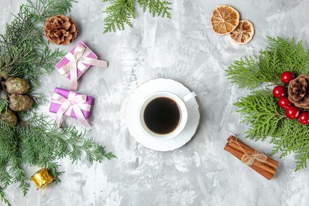 Widok z góry filiżanka herbaty świąteczne zabawki choinkowe gałęzie sosny laski cynamonu na szarym tle