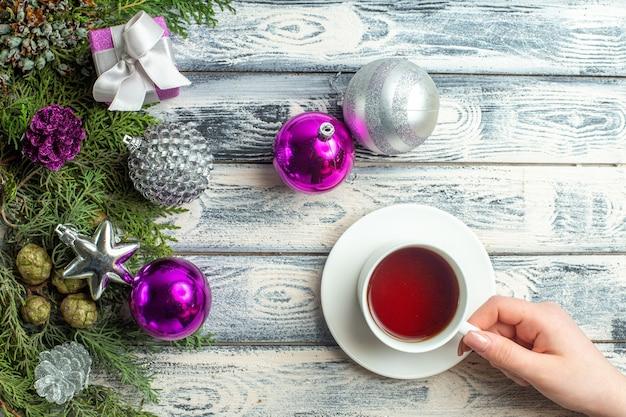 Widok z góry filiżanka herbaty w kobiecej dłoni mały prezent gałęzie jodły świąteczne zabawki na drewnianym tle