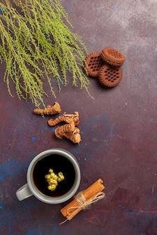 Widok z góry filiżanka herbaty wewnątrz płyty i filiżanka na ciemnej powierzchni napój herbaciany kolor zdjęcie słodkie