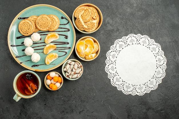Widok z góry filiżanka herbaty z ciasteczkami i cukierkami na szarej tabeli ciastko biszkoptowe