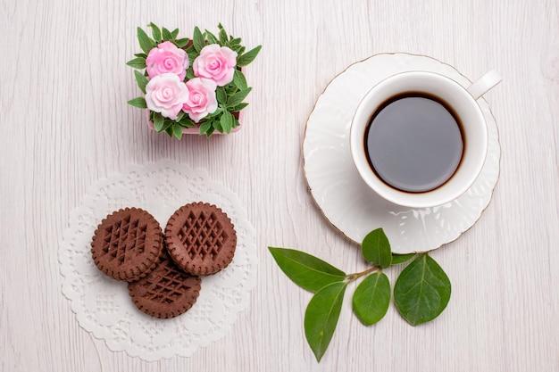 Widok z góry filiżanka herbaty z ciasteczkami na białym stole z cukrem ciasteczkami herbatnikami słodkimi herbatnikami