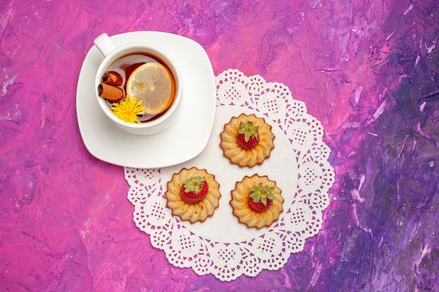 Widok z góry filiżanka herbaty z ciasteczkami na różowym stołowym herbatniku z herbatą w kolorze cukierków