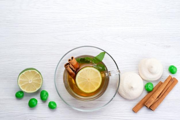 Widok z góry filiżanka herbaty z cukierkami cytrynowymi i ciasteczkami na białym, cukierki deserowe herbaty