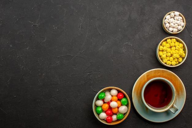 Widok z góry filiżanka herbaty z cukierkami na ciemnym biurku w kolorze tęczowego cukierka