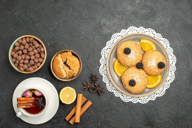 Widok z góry filiżanka herbaty z cynamonem i ciasteczkami na ciemnoszarej powierzchni ceremonia picia herbaty słodka