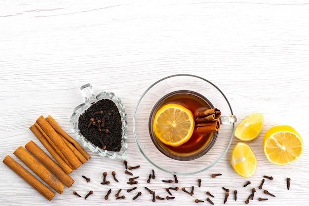 Widok z góry filiżanka herbaty z cytryną i cynamonem na białym, cukierków deserowych herbaty