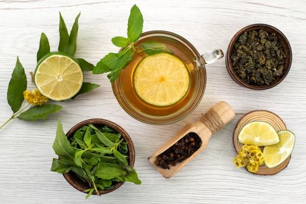 Widok z góry filiżanka herbaty z cytryną i miętą na białym, herbacianym cukierku deserowym
