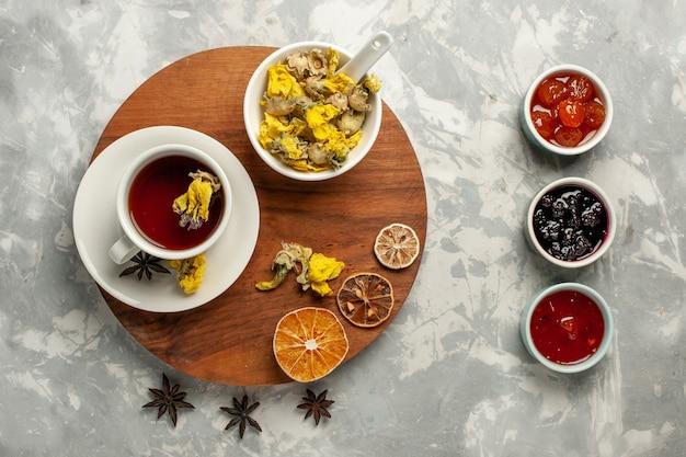 Widok z góry filiżanka herbaty z deserem i różnymi dżemami na białym backgruond dżem owocowy herbata słodki cukier