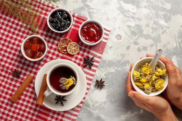 Widok z góry filiżanka herbaty z deserem i różnymi dżemami na lekkim białym backgruond owocowym dżemie herbata słodki cukier