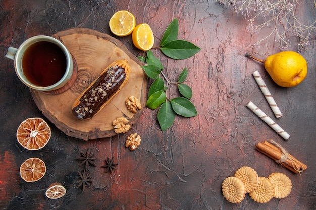 Widok z góry filiżanka herbaty z eklerką i ciasteczkami na ciemnym stole słodkie ciasto biszkoptowe