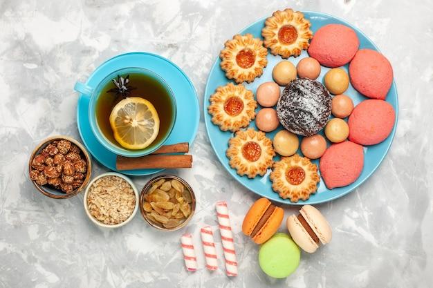 Widok z góry filiżanka herbaty z francuskimi ciasteczkami macarons i ciastami na białej powierzchni