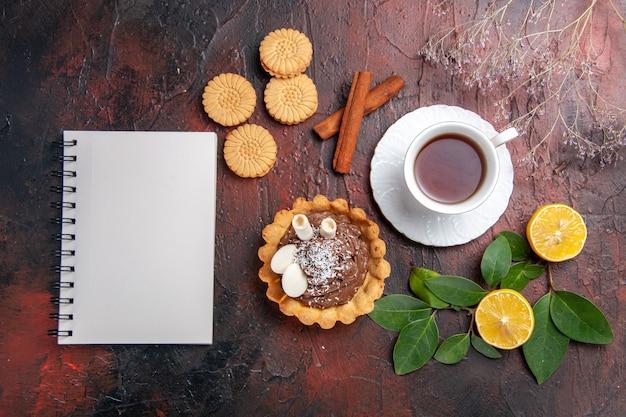 Widok z góry filiżanka herbaty z małym ciastem i ciasteczkami na ciemnym stole słodki deser herbatnikowy
