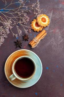 Widok z góry filiżanka herbaty z małymi ciasteczkami na ciemnym tle biszkoptowe ciastko ciastko cukier herbata