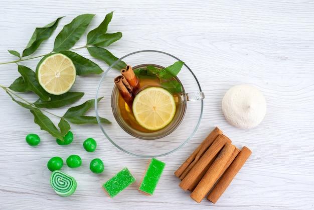 Widok z góry filiżanka herbaty z marmoladami cytrynowymi i cynamonem na białym, cukierków deserowych herbaty